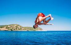 Mann springt Salto beim Baden beim segeln in Korfu mit Korfu Segeln