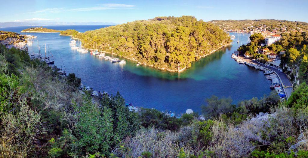 Blick über den Naturhafen von Gaios in der Abenddämmerung. Links der Nordkai, dahinter ganz links hinten die Insel Panagia und rechts davon in der Bildmitte oben Agios Nikolaos und rechts hinten der Westkai und das Südende des Hafens an der Stadtmitte