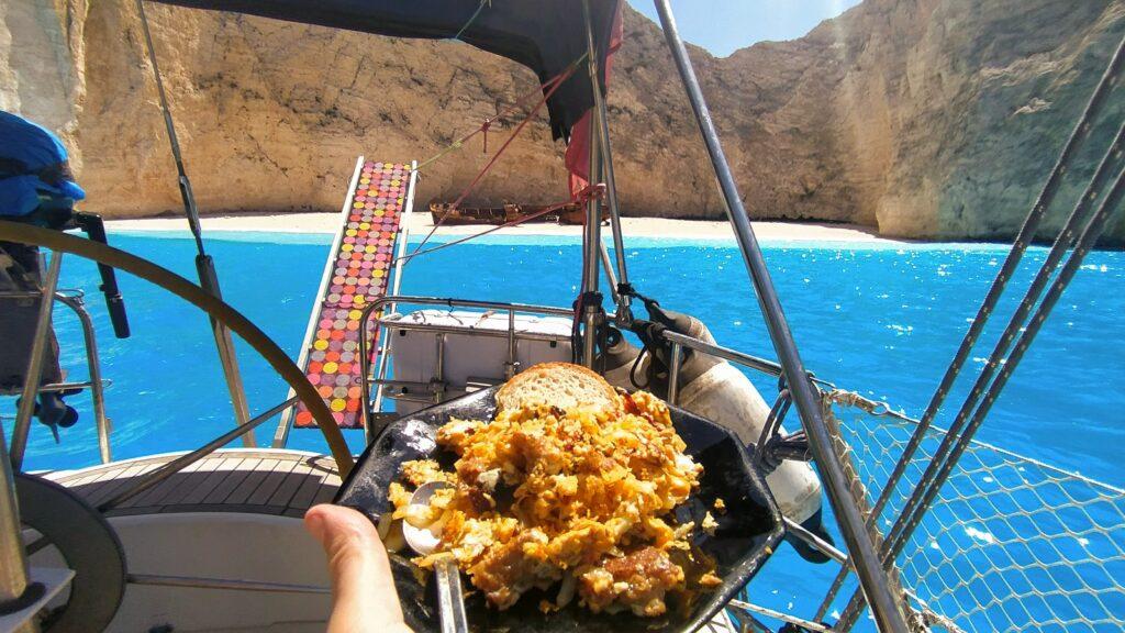 Leckeres Frühstück mit Eiern und Zwiebeln vor der menschenleeren Bucht von Navagio