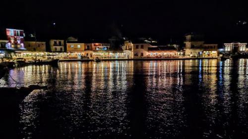 Longos bei Nacht mit stimmungsvollen Reflektionen in vielen Farben auf dem Wasser